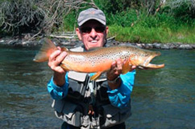 Fisherman showing off his caught rainbow trout with Three Rivers Resort & Outfitting in Gunnison, Colorado