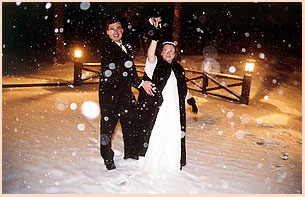 Just married couple celebrating in the snowfalkes in Colorado