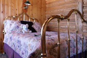 Interior of romantic and cozy room with brass bed at Allenspark Lodge in Allenspark, Colorado