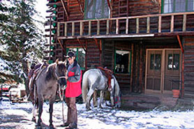 Man with horse in front of Allenspark Lodge with snow on the ground, near Estes Park Colorado