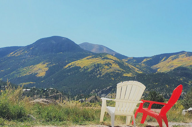Chairs at Alpine Moose Lodge overlooking view of San Juan Mountains near Lake City, Colorado