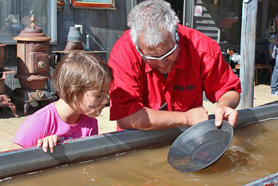 Man showing girl how to pan for gold. Discover your inner prospector as you pan for gold and gemstones at Argo Gold Mill Museum in Denver Mountain Area, Colorado.
