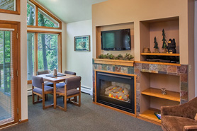 Interior of cabin living room with fireplace and dining table at Aspen Winds on Fall River
