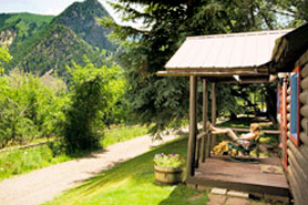 Woman relaxing on cabin porch at Avalanche Ranch Cabins and Hot Springs in Crystal River Valley near Glenwood Springs, Aspen, and Snowmass Village, Colorado