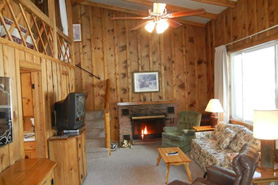 View of living area inside log cabin with tv, loft and fireplace at Blackhawk Cabins in Estes Park, Colorado.
