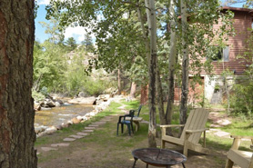Relaxing shaded sitting area behind cabins along riverside path at Blackhawk Cabins in Estes Park, Colorado.