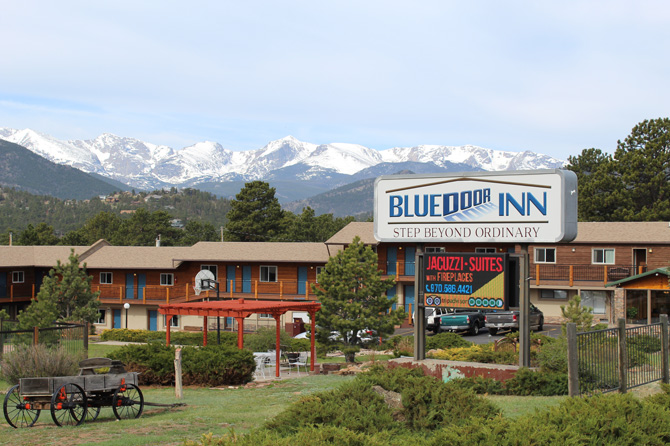 Front of Blue Door Inn with mountians in background in Estes Park, Colorado