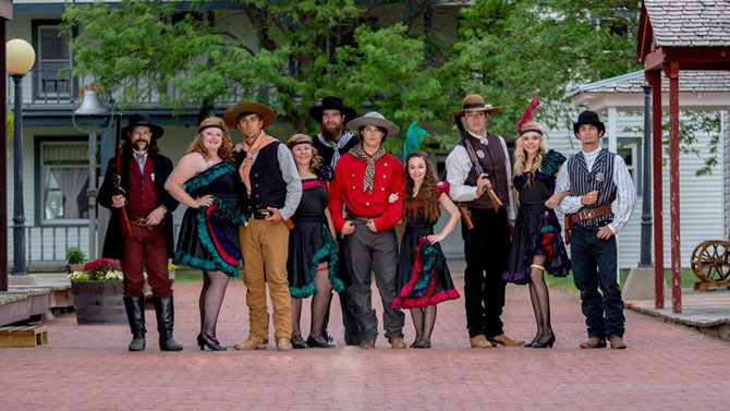 A cast of wild west gunslingers and cancan dancers on the street of Burlington Old Town Museum a old western town in Eastern Colorado