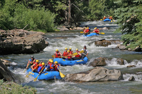Rafts from Clear Creek Rafting Company float down the Arkansa River near Royal Gorge, Colorado