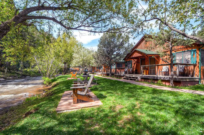Relaxing lounge chairs and cabins by a river at Bear Creek Cabins near Evergreen, Colorado