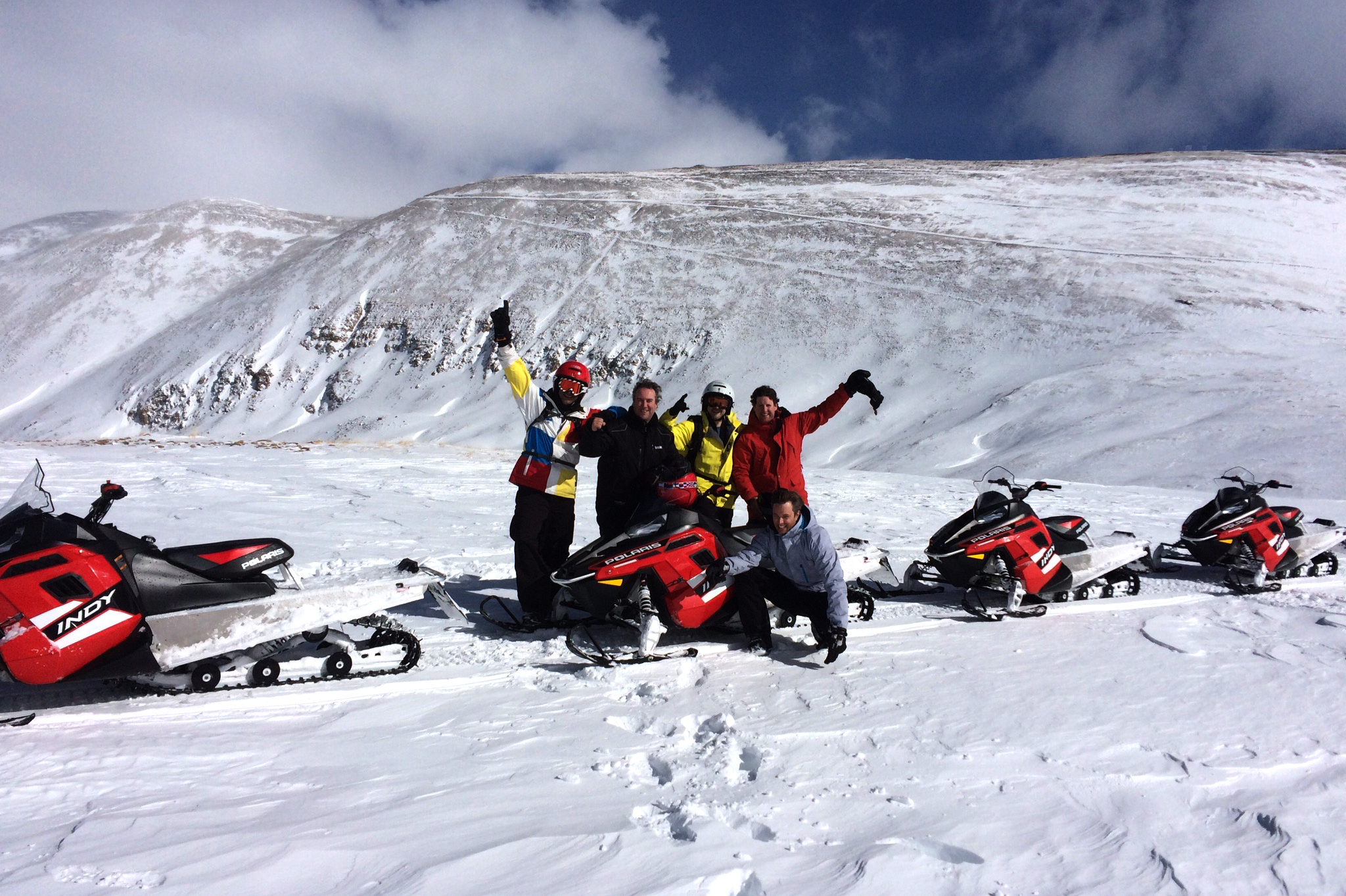 Group of snowmobilers with High Country Tours on a mountain ridge in Summit County
