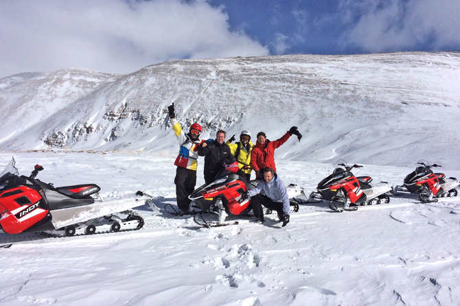 Group of snowmobilers with High Country Tours on a mountain ridge in Summit County, Colorado