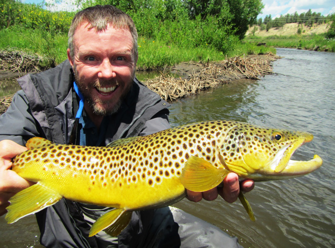 Fisherman showing off his catch with Colorado Tout Hunters Fly-Fishing Guide in the Denver Mountain Area