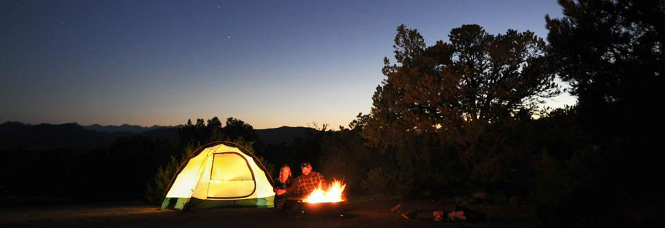 Two campers snuggling by campfire and tent at Echo Canyon Campground in the Royal Gorge Area