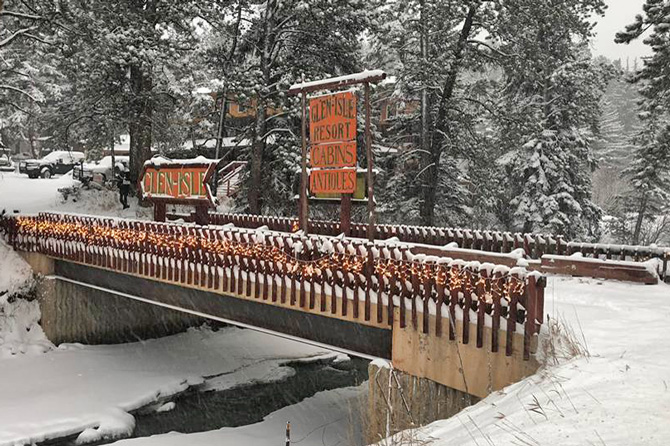 Bridge crossing a snowy river at Glen-Isle Resort Lodge and Cabins near Bailey and Pine, Colorado