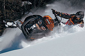 Snowmobiler bursting through snow drift in Grand Lake, Colorado