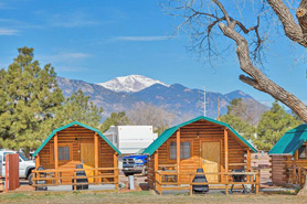 Cabins in front of mountains with Colorado Springs KOA in Colorado Springs, Colorado. View Pikes Peak with a cabin for  your camping adventure. Evening campfires!