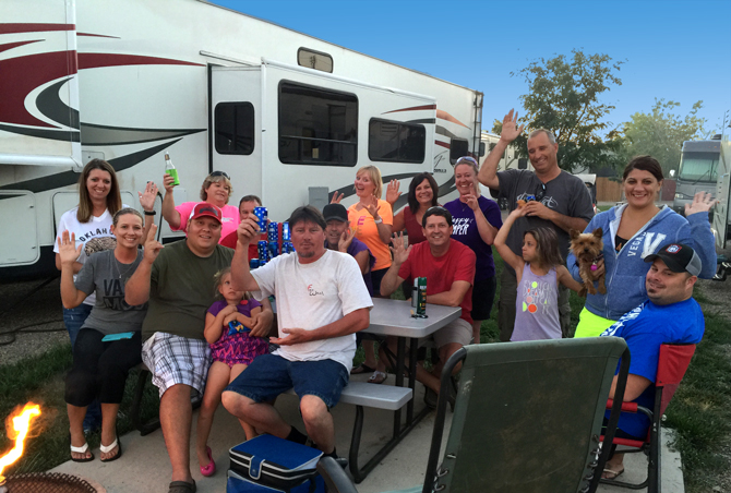 A fun group of people by campfire and RV site at the La Junta KOA
