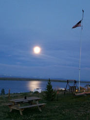 Moon rising over lake and picnic area at Lake John Resort RV Park and Cabins in Walden, Colorado