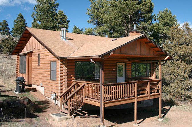 A cottage with a balcony with Lazy R Cottages in Estes Park, Colorado. Cozy and Rustic Cabins. Decks, Fireplaces, Mountain Views. 1 Mile from Rocky Mountain National Park.