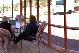 People sitting inside a screened in porch at Lost Burro Camping and Lodging in Cripple Creek, Colorado