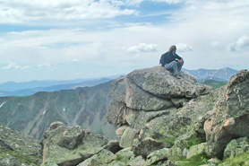 Hiker purched on a rocky seat near Winter Park, Colorado