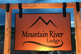 Mountain River Lodge entrance sign at dusk in Lake George, Colorado
