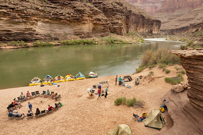 People camping and preparing to raft on the shore of a river with O.A.R.S. Colorado Rafting, Authorized Concessionaire of Dinosaur National Monument, near Dinosaur, Colorado