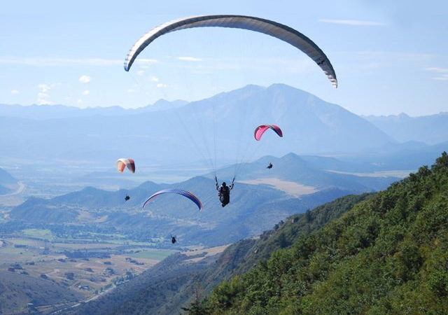 Paragliders with Adventure Paragliding floating of the side of a mountain near Glenwood Springs Colorado