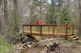 Woman standing on bridge near tent sites at Archer's Poudre River Resort in the Poudre River Valley near Fort Collins, Colorado