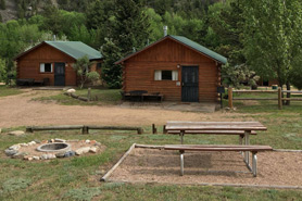 A couple of cabins with fire pit at Archer's Poudre River Resort in the Poudre River Canyon near Fort Collins, Colorado