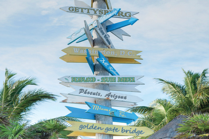 a cross road of signs at a tropical paradise representing Blue Sky RV Insurance in the Denver area of Colorado