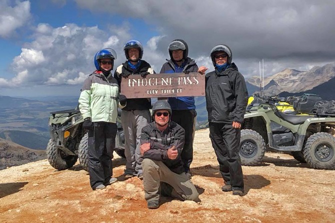 Five people standing by Imogene Pass sign with ATVs rented from San Juan Backcountry Tours and Rentals, in the Silverton Area, Colorado