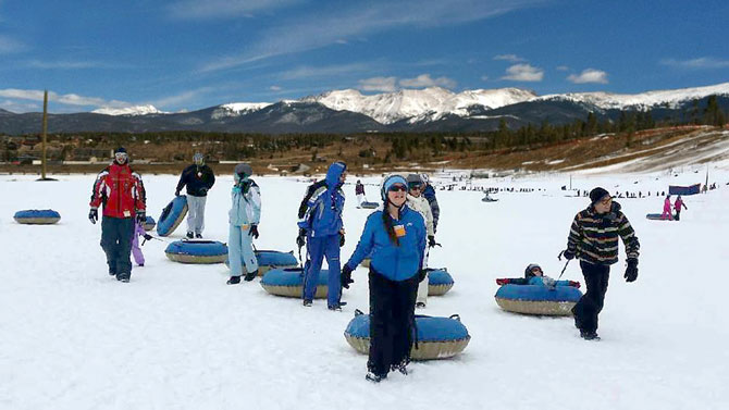 Group of people bundled up and having fun Snow tubing at Colorado Adventure Park in Winter Park, Colorado