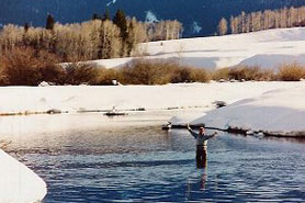 Winter fisherman wading in water with Sleepy Cat Mountain Lodging in Meeker Colorado