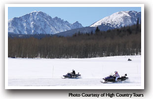 Snowmobiling in Summit County, Colorado with mountains in the background, photo courtesy of High Country Tours