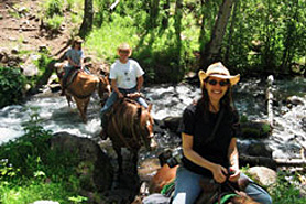 Horseback riding group crossing a creek from Sweetwater Lake Resort in Sweetwater, Colorado