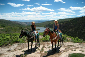Two horseback riders from Sweetwater Lake Resort over looking White River in Colorado