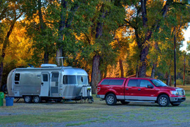 Truck with travel trailer under fall trees in RV Park with Twin Rivers Cabins and RV Park, west of Antonito, Colorado. Beautiful shaded RV park and tent sites.